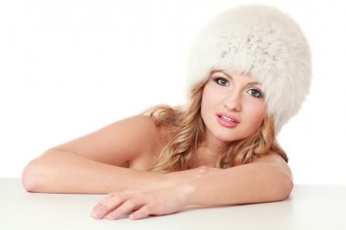 Beauty fashion model girl in a fur hat.