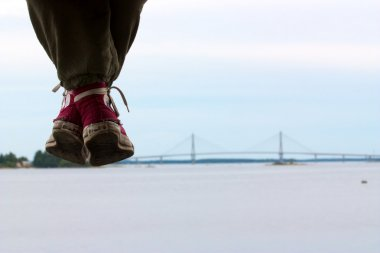 Girls legs with red used converse shoes hanging down and bridge on horizon