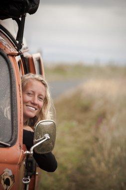 Blonde young girl travelling in vintage camper van