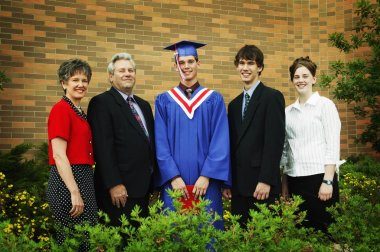 Graduate Poses For Family Photo