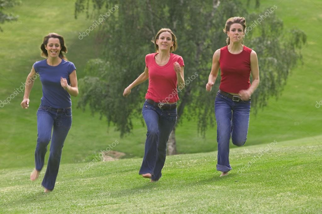 Three Teen Girls Running In Park