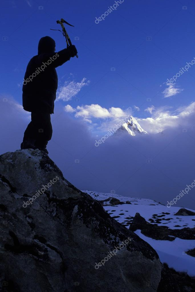Mountaineer On Peak With Mountain Peak Rising Out Of Clouds In Background