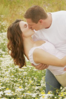 Couple Kiss In A Field Of Daisies