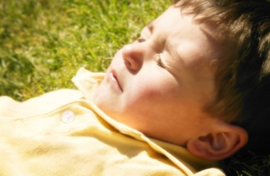 A Young Boy Lying In The Sun