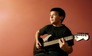 Child Holds A Guitar