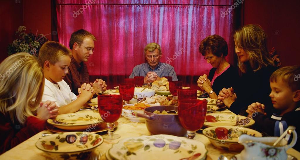 family praying around table - 1400×750