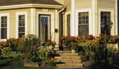 The Front Entrance Of A House With A Flower Garden