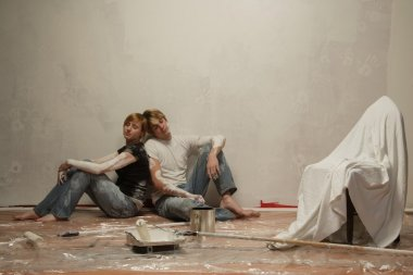 Couple Rests After A Hard Day Of Painting