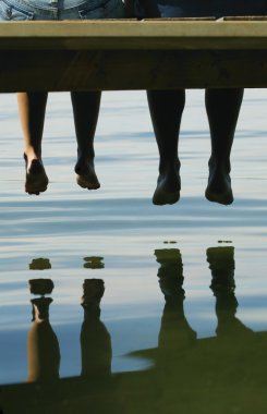 Two People Dangling Their Feet Off A Dock