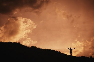 Silhouette Of Man Standing With Arms Outstretched