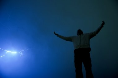 Man With Outstretched Arms In Lightning Storm