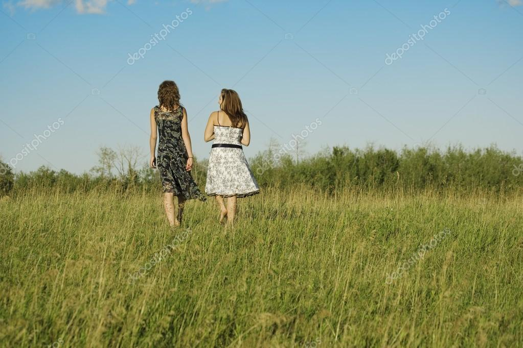 Two Women Walking In Grassy Field