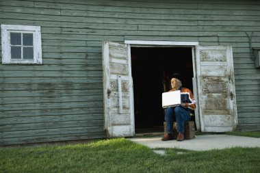 Man Working On Computer Outside Of Barn Or Shed
