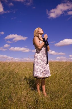 Woman Praying In A Field