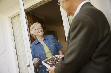 Man Offering A Box Of Chocolates To Woman