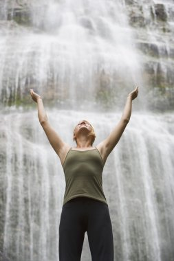 Woman With Arms Raised In Front Of Waterfall