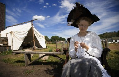 Woman In Period Costume Crocheting
