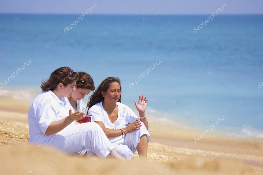 A Group Of Women Unite In Prayer On The Beach