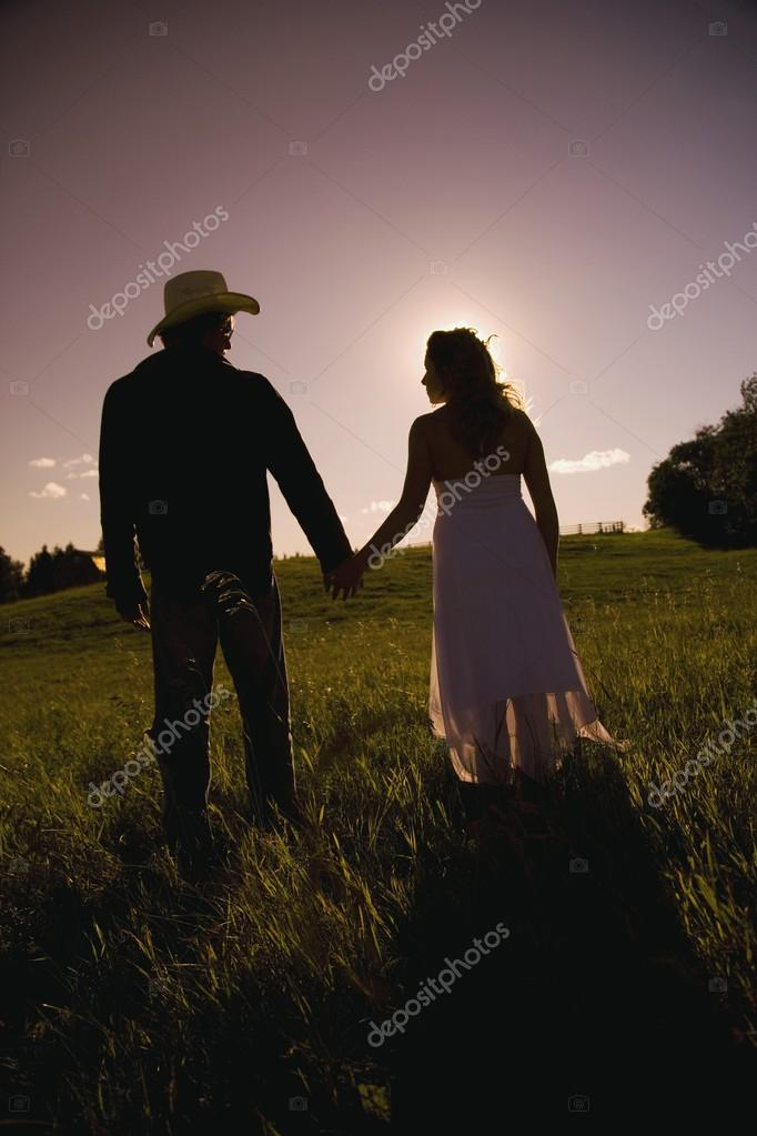 Man And Woman Walking Hand-In-Hand In Field In Sunset