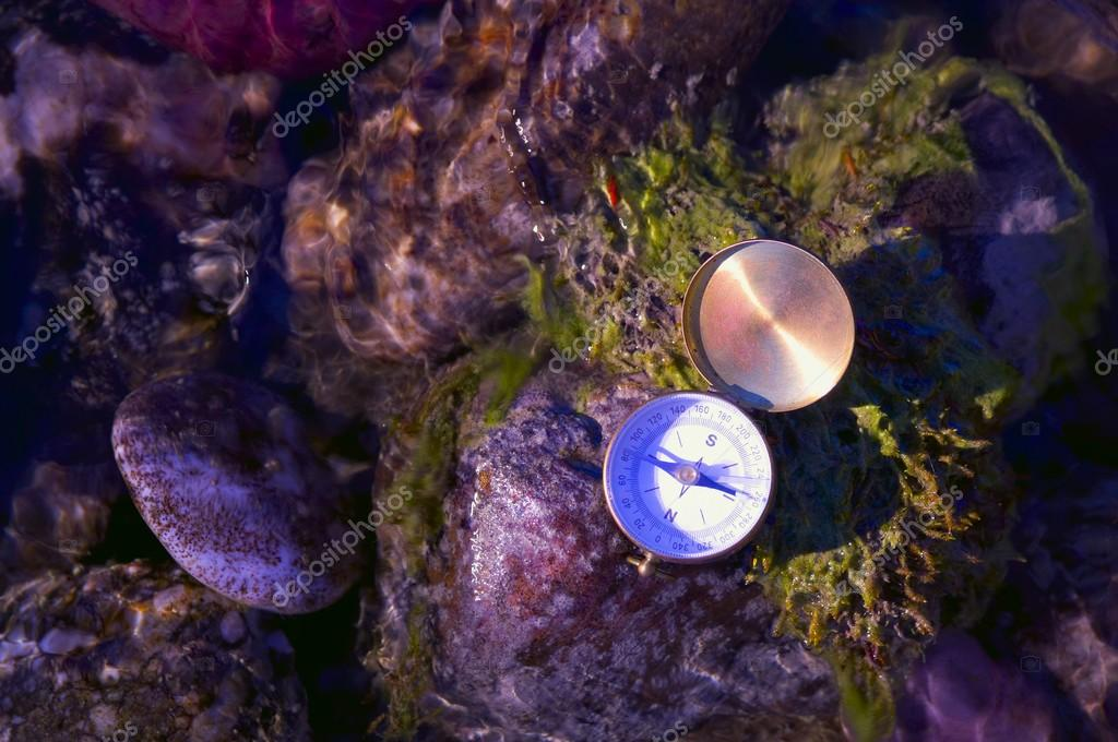 A Compass On River Rocks