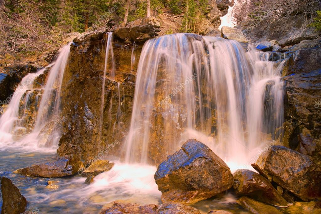 Waterfall Flowing Over Rugged Terrain