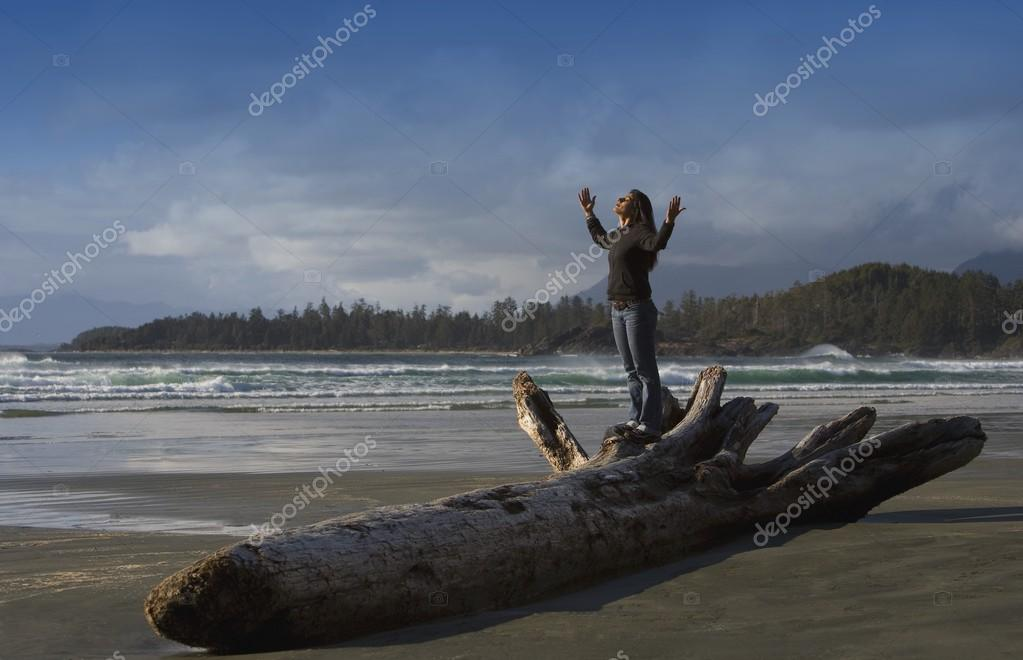 A Woman Raises Her Hands On The Beach