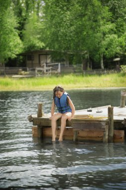 Young Girl Sitting On Dock