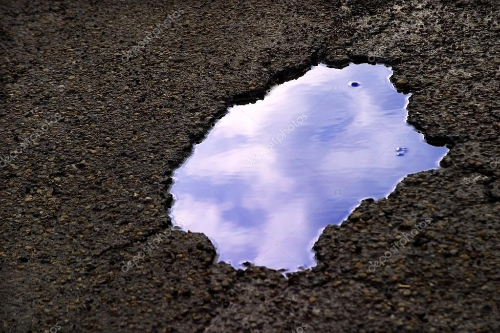 Clouds Reflecting In Puddle
