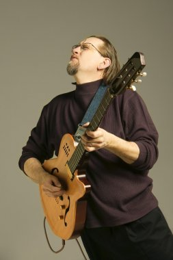 Middle Aged Man Playing Guitar Looking Upwards