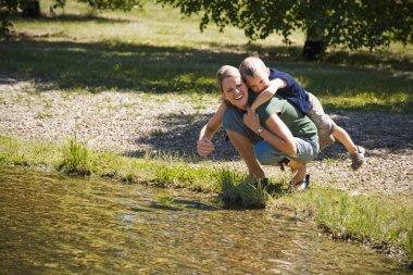 Mother Giving Son Piggyback Near Lake