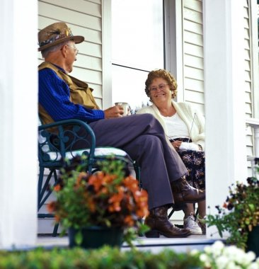 An Elderly Couple Sitting On A Porch