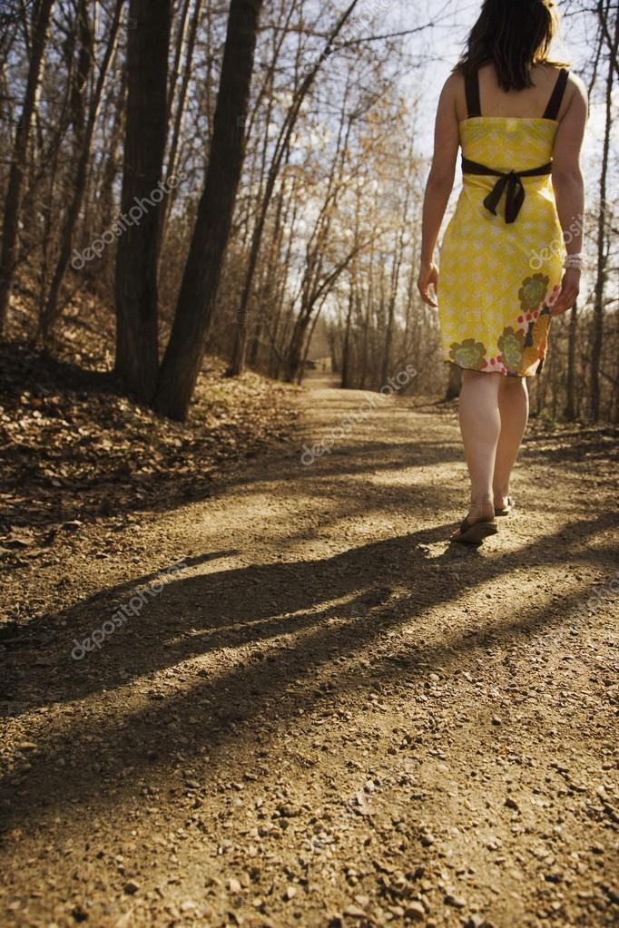 Rear View Of Woman Walking On Gravel Pathway