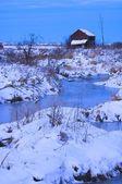 baracca abbandonata nei pressi di un torrente ghiacciato in inverno