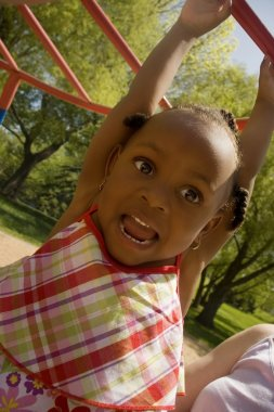 Young Girl Hanging From Playground Equipment
