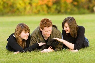 Teenagers Petting A Dog