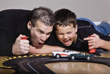 Father And Son Playing With Race Cars