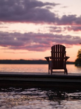 Lake Of The Woods, Ontario, Canada. Empty Deck Chair On A Pier Next To A Lake