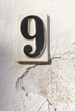 Ceramic number nine on whitewashed wall