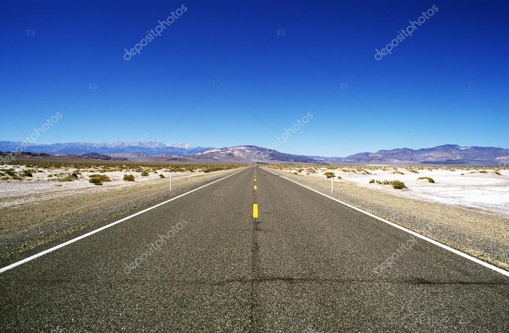Road Leading Through Barren Landscape To Mountains