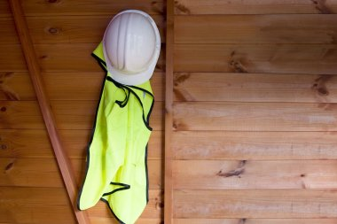 Reflective Vest And Hardhat Hanging On Wall
