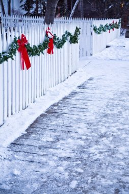 Christmas Garland And Red Bows On A White Picket Fence