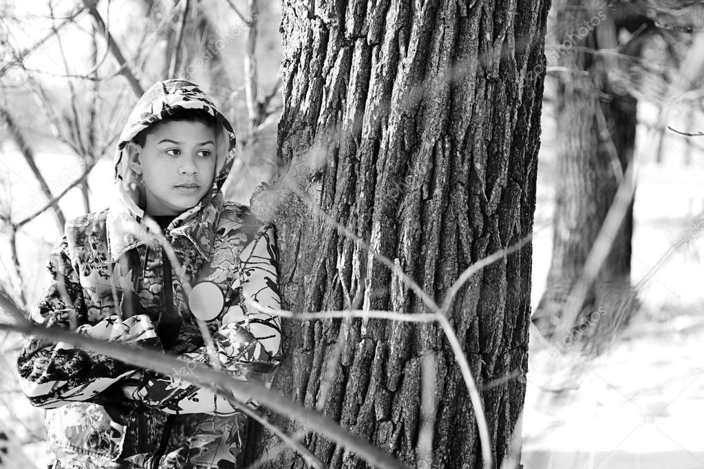 Teenage Boy Hunting In A Snow Covered Wooded Area