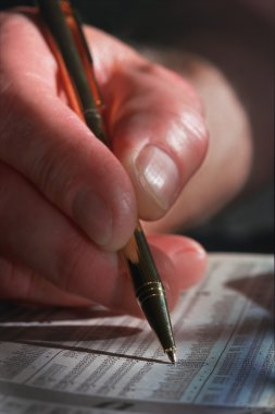 Closeup Of Man's Hand And Pen Circling Investment In Newspaper