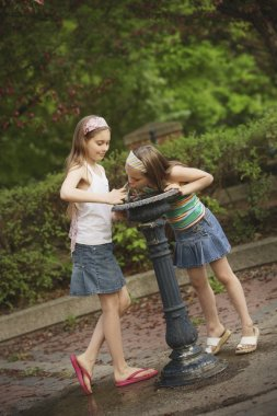 Two Girls At A Drinking Fountain