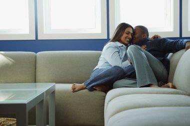 Couple Snuggles On Sofa