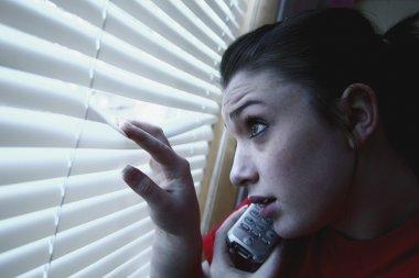 Teenage Girl On The Phone, Peeking Out A Window
