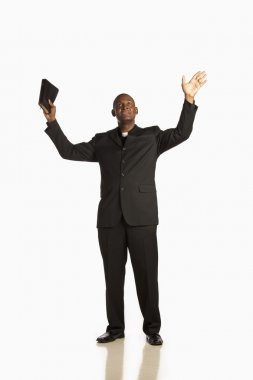 Man Wearing A Clerical Collar And Holding His Bible Up