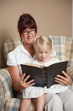 Grandmother Reading The Bible To Her Granddaughter