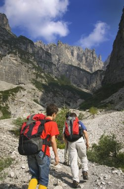 Male Hikers Climbing With Backpacks Up The Dolomites. Veneto, Italy