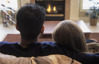 Couple Snuggles By Fireplace